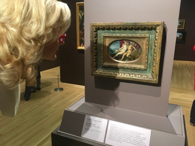 Rachelle Siegrist looking at a miniature cabinet painting