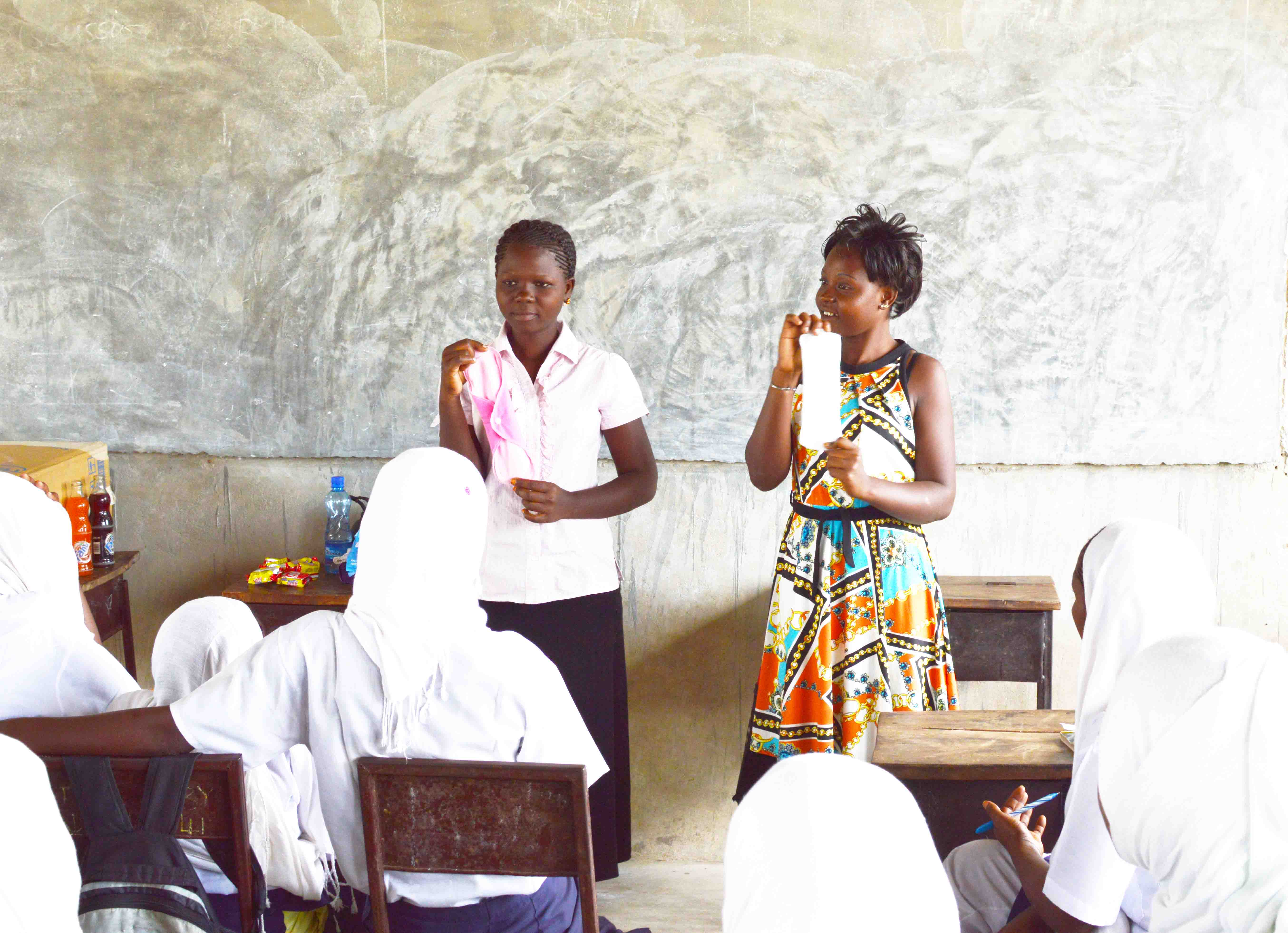TRLF youth, Nancy an Esther explaining the use of reusable sanitary napkins to students from Kitere