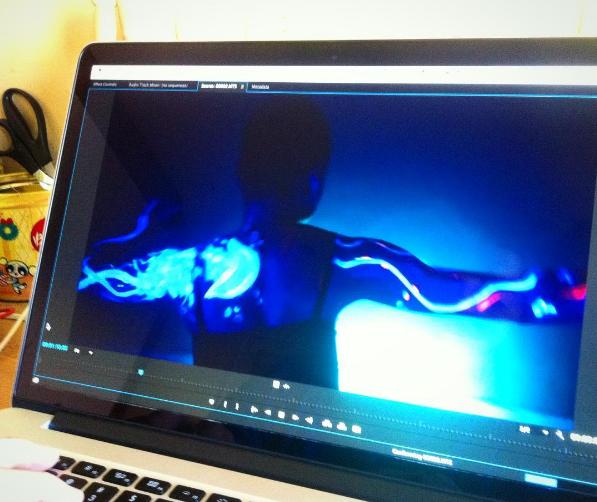 Imagem de um computador, aberto em um programa de edição de vídeos. Na tela, Mirelle de costas, com uma forte luz azul desenhando sua silhueta.