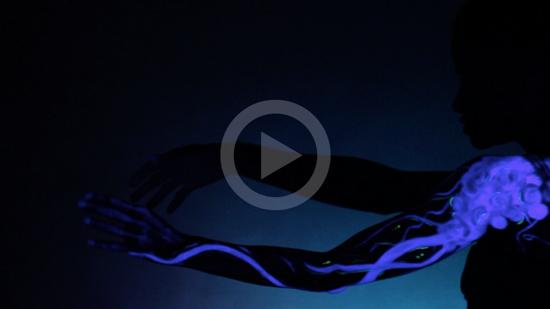 Imagem de miniatura do vídeo: a silhueta de uma mulher com tentáculos brilhantes pintados no braço. Clique para assistir.