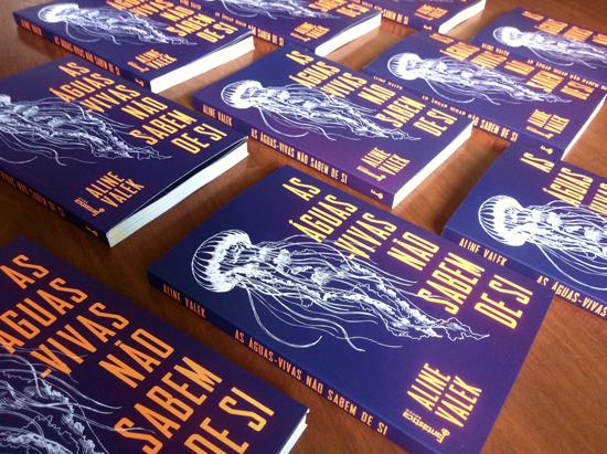 """Livros dispostos como um enxame de águas-vivas. Na capa, com o desenho de uma água-viva branca em contraste com o fundo roxo, é possível ler """"As águas-vivas não sabem de si"""""""