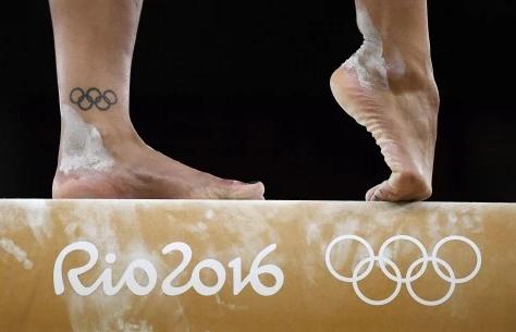 """Imagem dos pés de uma ginasta, sujos de pó de magnésio, se equilibrando sobre uma trave com a inscrição """"Rio 2016"""". No tornozelo da atleta, uma tatuagem com os anéis olímpicos"""