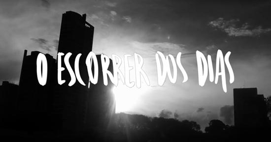 """Imagem em preto e branco da silhueta de um prédio desenhada pelo pôr-do-sol. Sobre a imagem, o título """"O escorrer dos dias""""."""