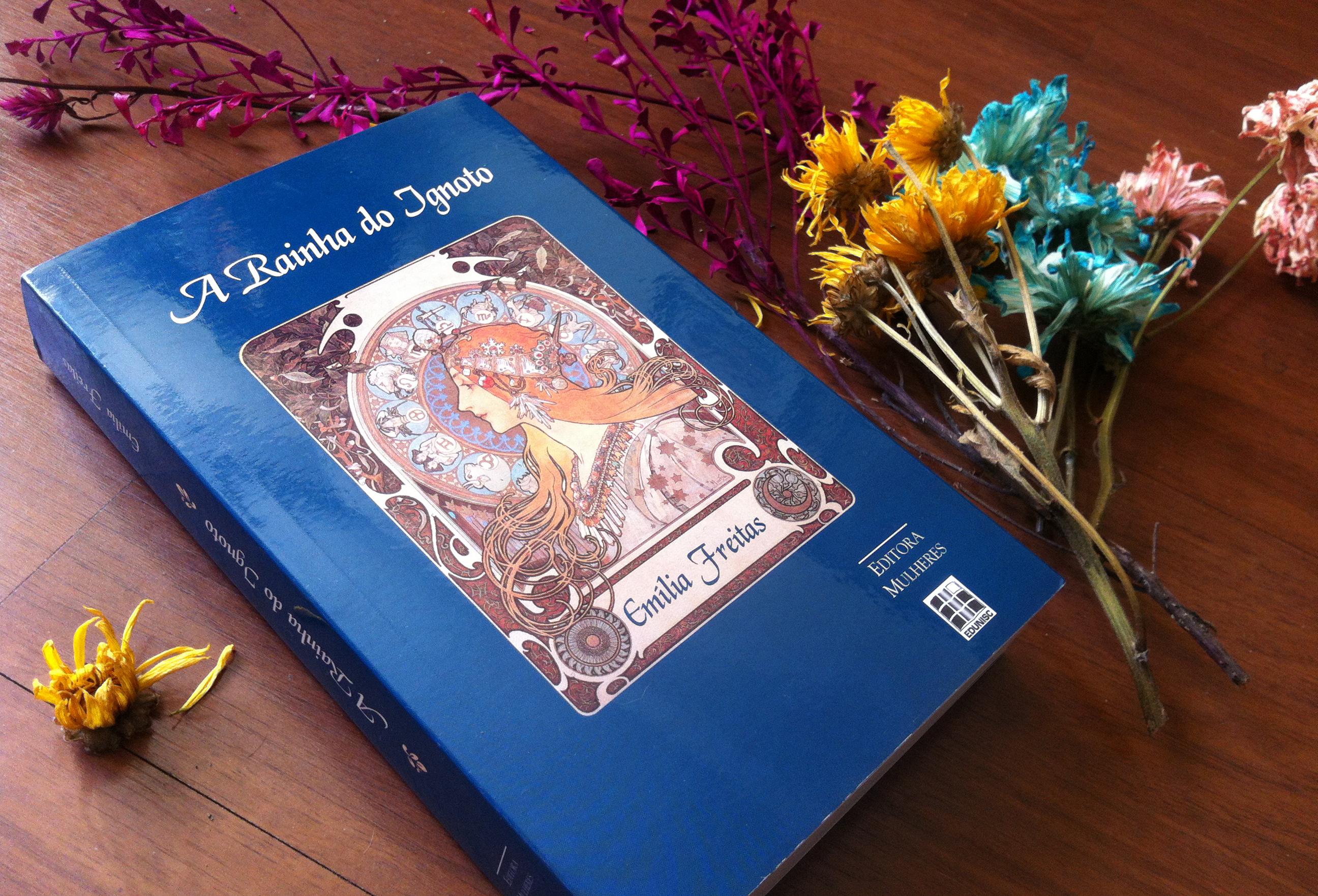 """A capa do livro """"A Rainha do Ignoto"""", de Emília Freitas, cercada de flores secas e coloridas."""