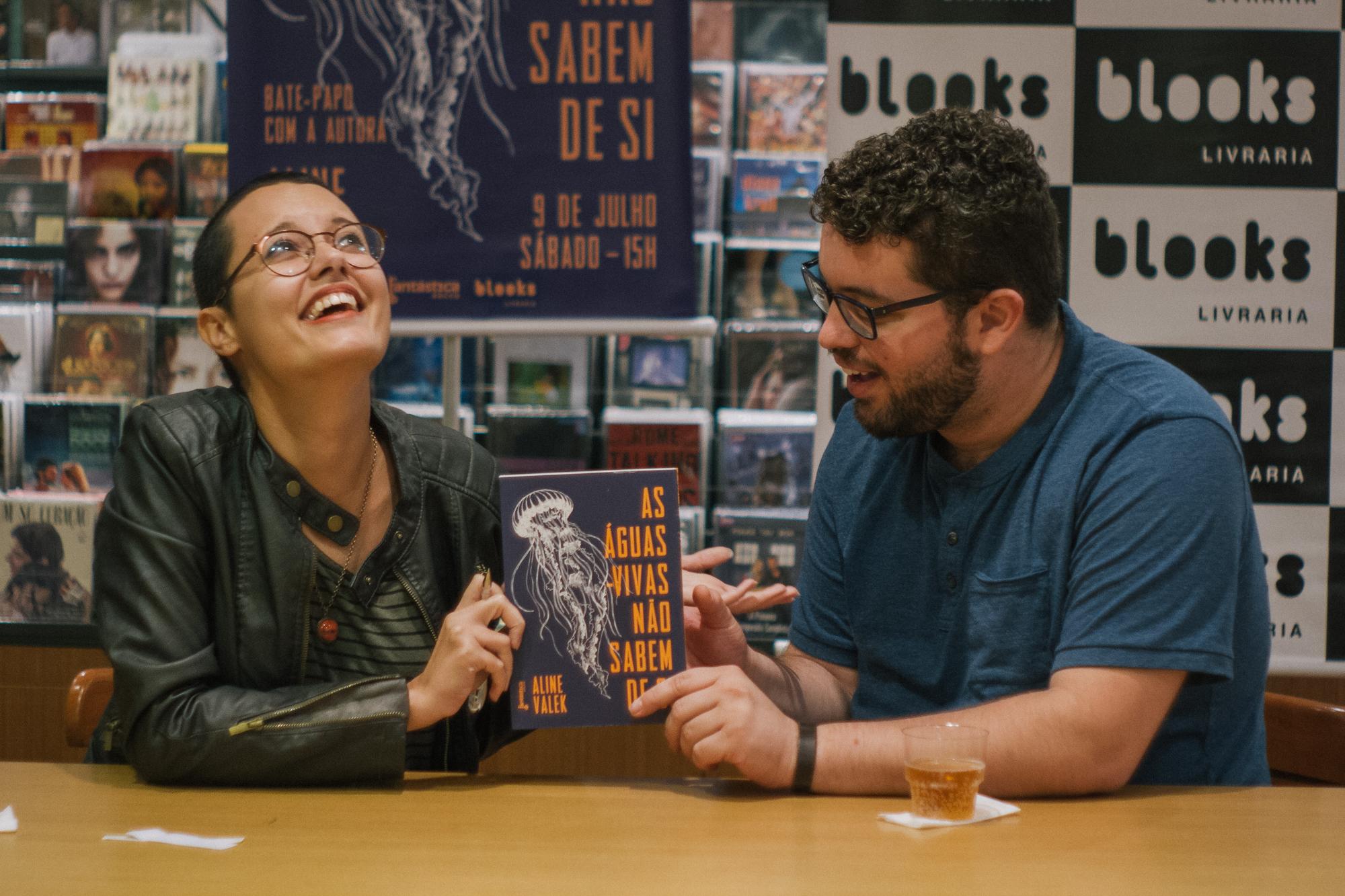 foto em que sorrio super naturalmente ao lado de um leitor que também segura o livro super naturalmente