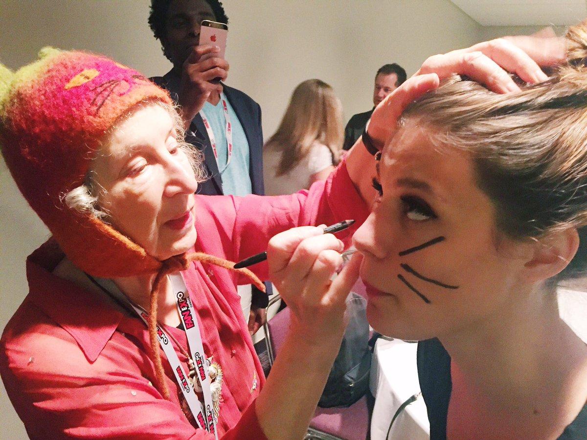Imagem da escritora Margaret Atwood, com seus 76 anos, vestindo uma touca rosa de gatinho e pintando, com um lápis de maquiagem, bigodes de gato no rosto de uma mulher, no meio de um evento. Atrás delas, um cara tira foto do momento com o celular.