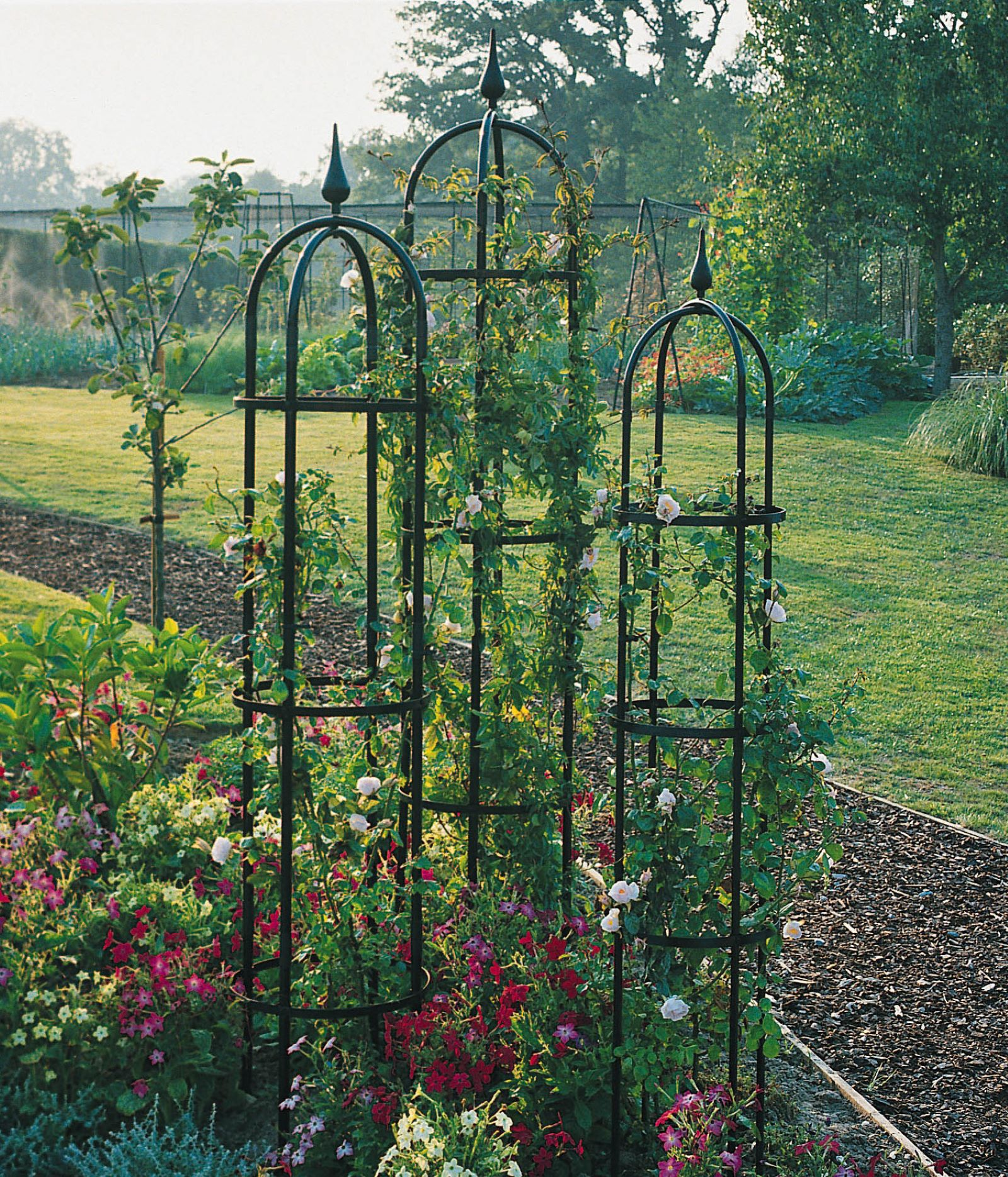 A trio of rose pillars can hide an ugly yard pipe or electric box