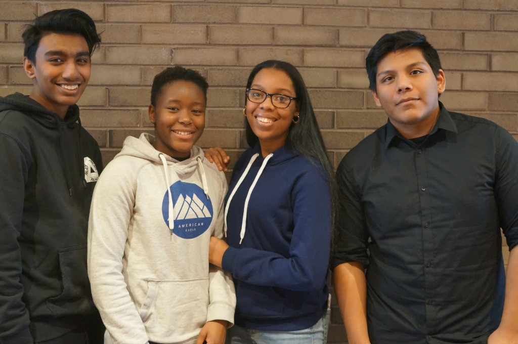 Four students face the camera and smile.
