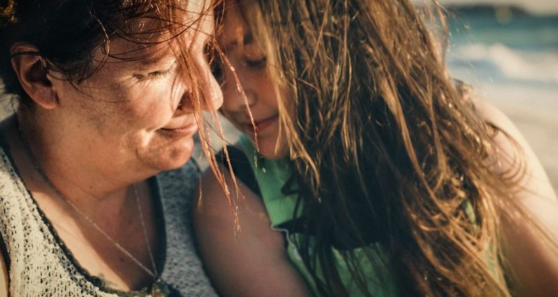 Woman sitting on the beach with her daughter, her face in warm sunshine, looking calm and at peace.