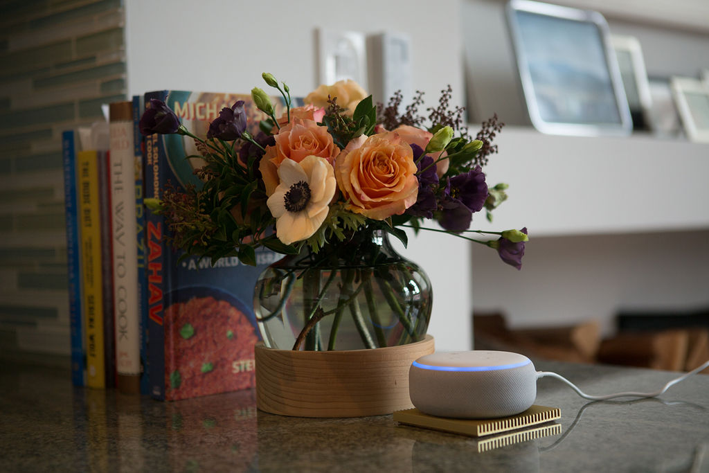An Echo Dot on kitchen counter with flowers