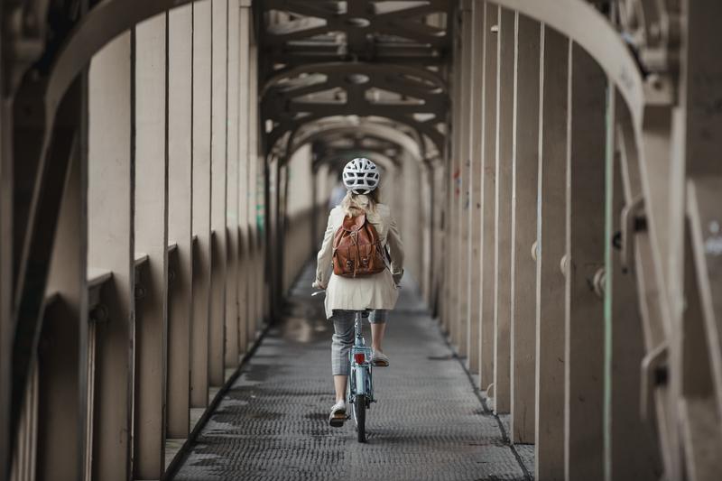 Woman biking on a bridge