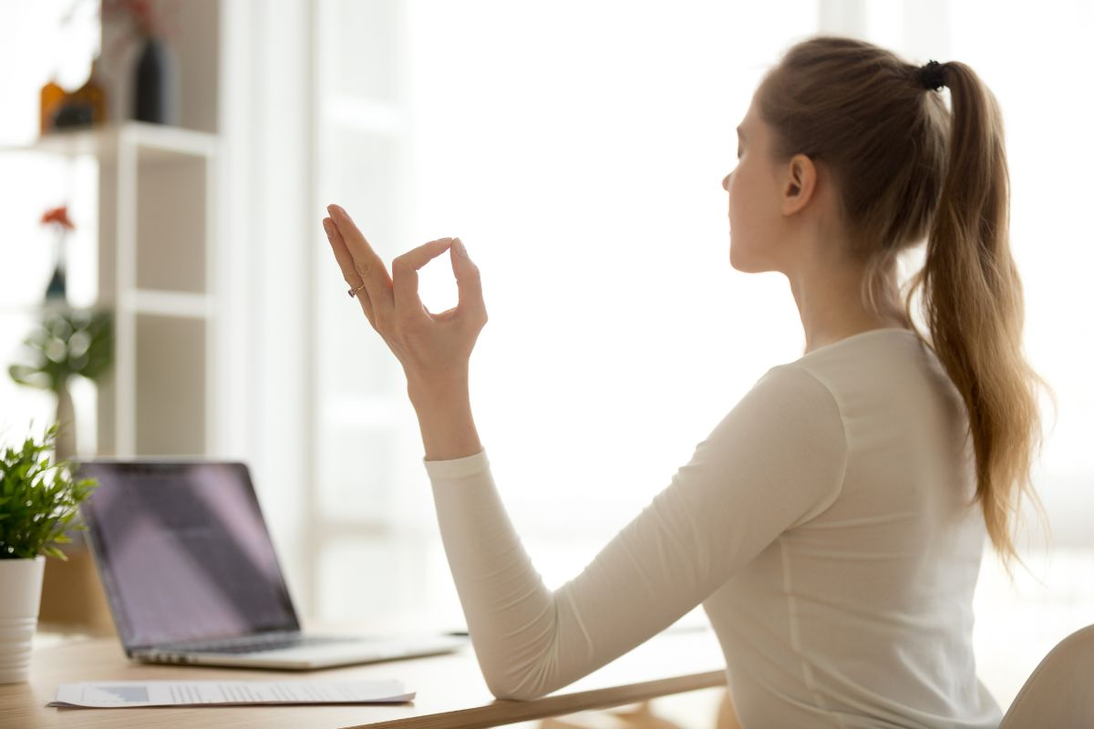 A woman doing yoga at her desk