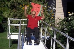 Mature gentleman using a wheelchair and using a ramp at the rear of his house