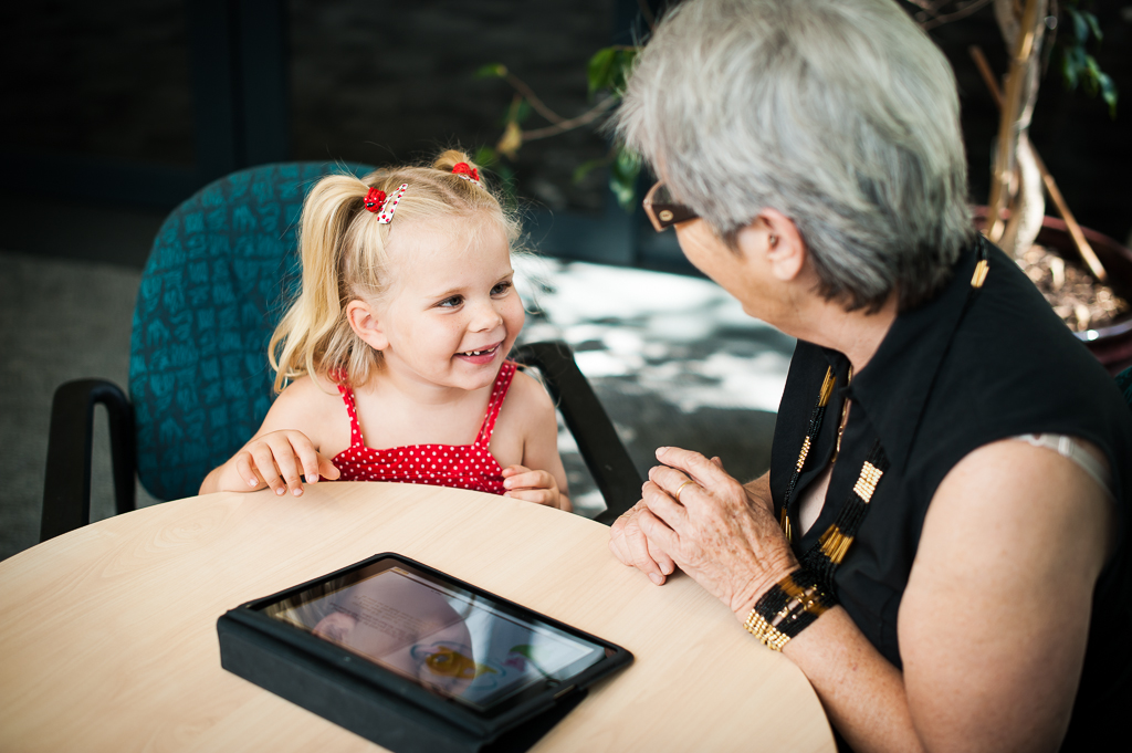 Mature lady seated beside a young child with an iPad in front of them