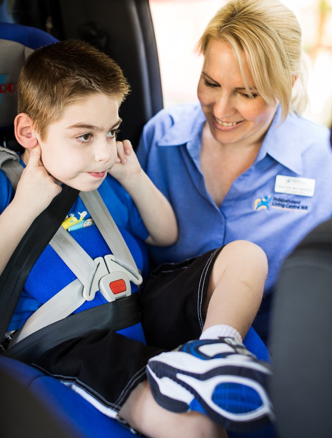 A image of a young child being seated in a child restraint in a car with a ILC OT assisting