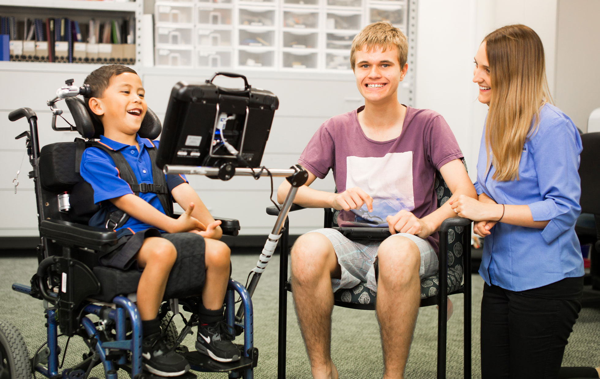 Two young students seated side by side using their assistive technology with an ILC therapist