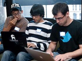 3 young men looking at laptop computer screens