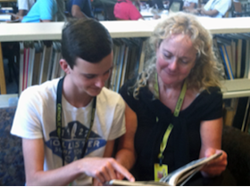 Teacher and student reading book together