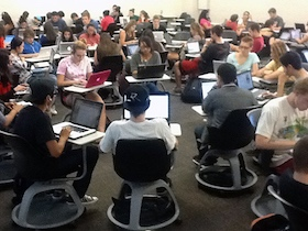 Group of students sitting in desks forming a circle
