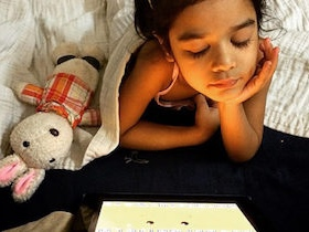 Young girl looks at ipad from bed