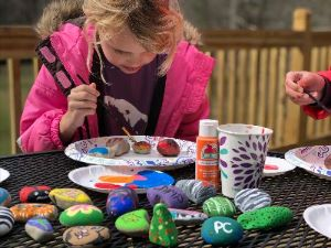 Child paints rocks at Project Chimps