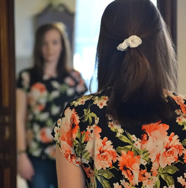 photo: young woman looking at herself in the mirror
