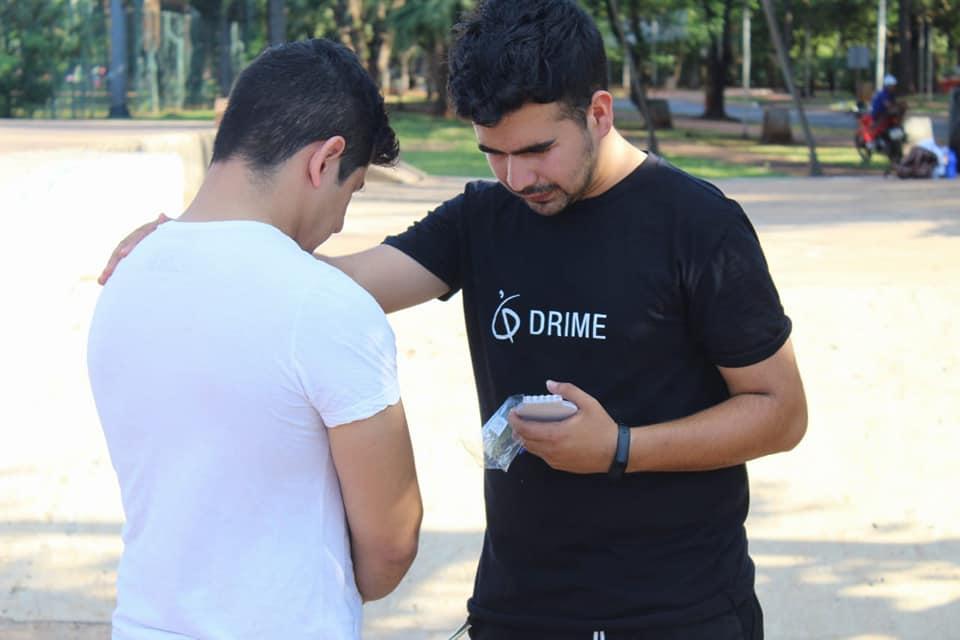 A DRIMER praying with a man in Ciudad del este