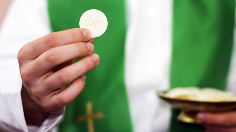 Close shot of a priest holding a Communion wafer.