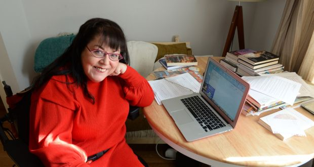 Rosaleen sits at a desk covered with books and paper and an open laptop.
