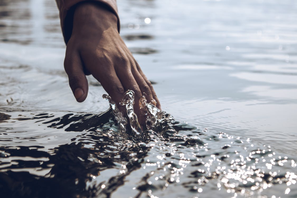 A hand skims across the surface of the water.