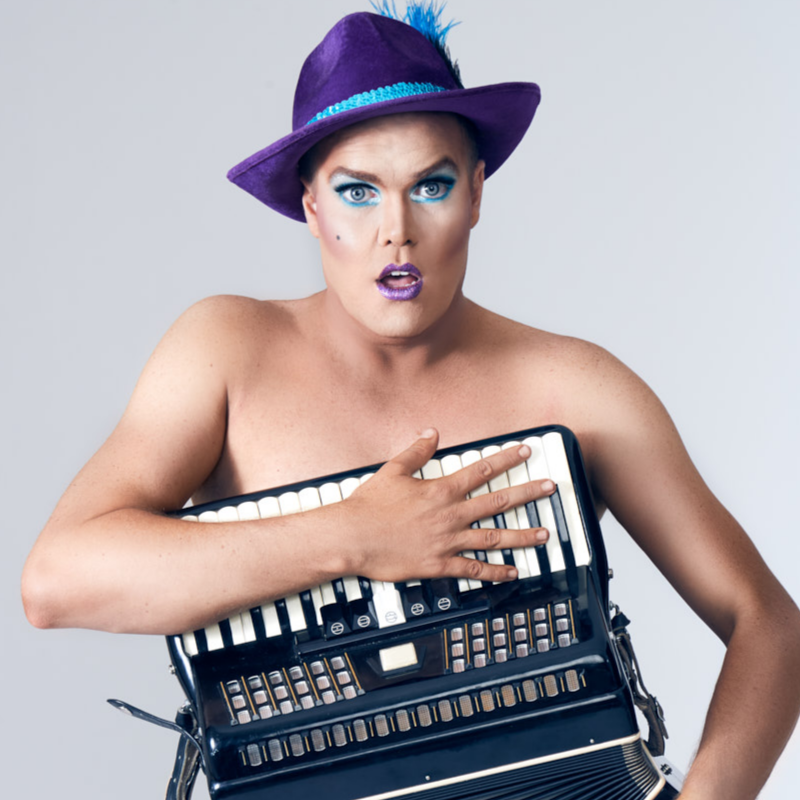 Hans wears a purple hat with a blue trim and matching blue eyeshadow and purple lipstick. He clutches an accordion across his bare chest.
