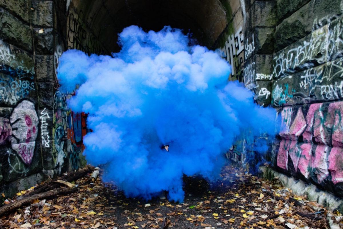 A cloud of blue smoke engulfs a graffiti-covered alley