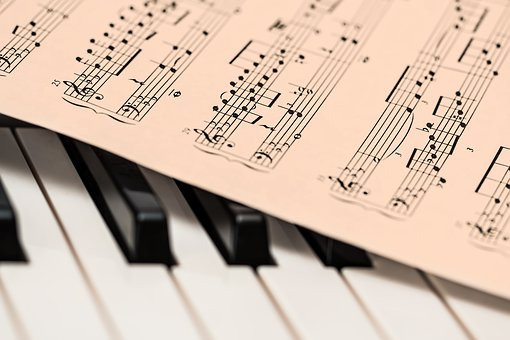 A sheet of piano music lays on top of piano keys.