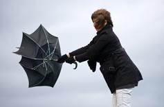 Femme essayant de maintenir son parapluie sous un vent violent