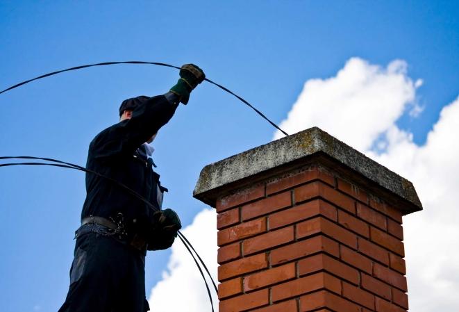 Homme équipé de gants en train de ramoner une cheminée en briques rouges