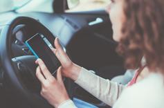 Conductrice entrain de consulter son smartphone dans sont véhicule à l'arrêt