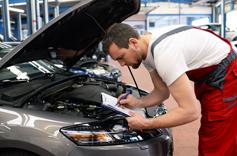 Garagiste en train de noter des information sur le capot d'une voiture
