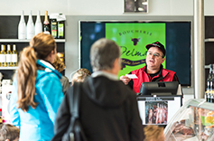 Un boucher au comptoir de sa boutique recevant des clients