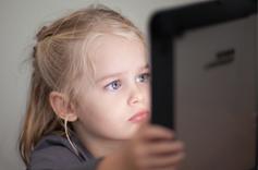 Jeune fille entrain de regarder un écran