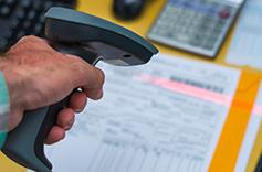 Une main tenant un scan pour scanner un code-barre