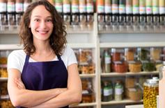 Commerçante souriante dans son magasin devant des distributeurs alimentaires en libre service