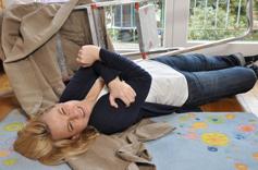Femme victime d'une chute à son domicile depuis un escabot, tenant son épaule de douleur