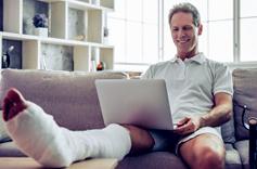 Homme avec une jambe dans le platre assis sur un canapé avec un ordinateur sur les genoux