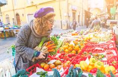 Jeune femme vegan entrain d'acheter des légumes au marché un jour ensoleillé