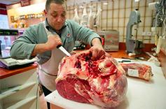 Boucher-charcutier en train de découper de la viande