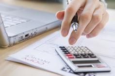 Main de femme en train de faire des calculs sur une calculatrice