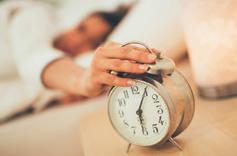 Femme entrain d'éteindre son réveil à 6h05
