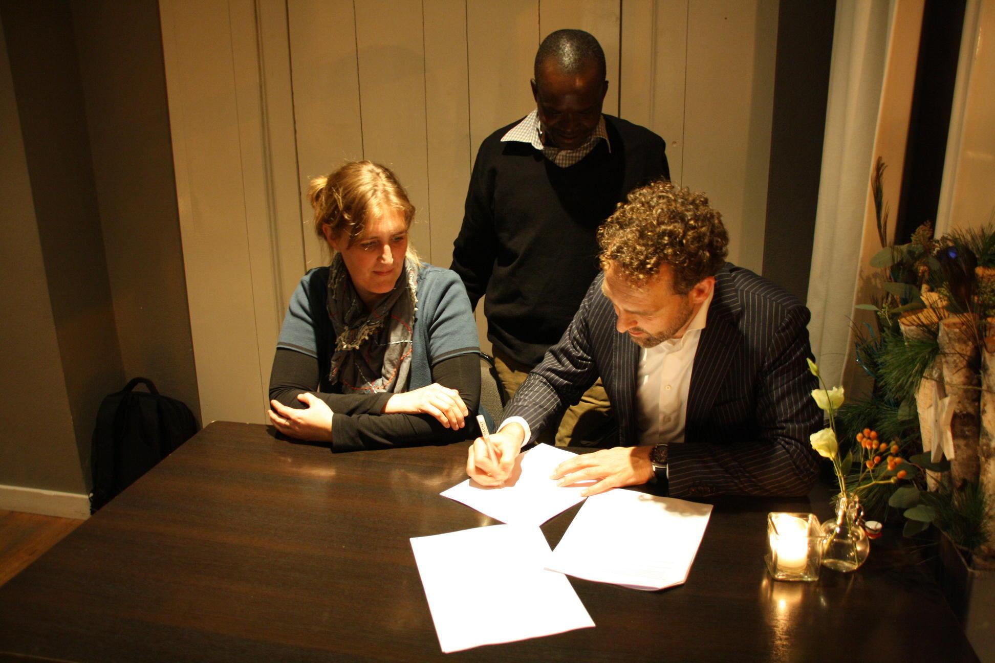 De ondertekening van de overdracht op 30 november, in bijzijn van Justine Ojambo.