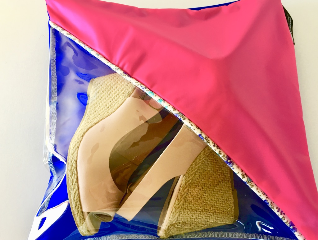 A lovely pink and royal blue shoe pouch with diagonal transparent window, a hanging loop and zip closure.