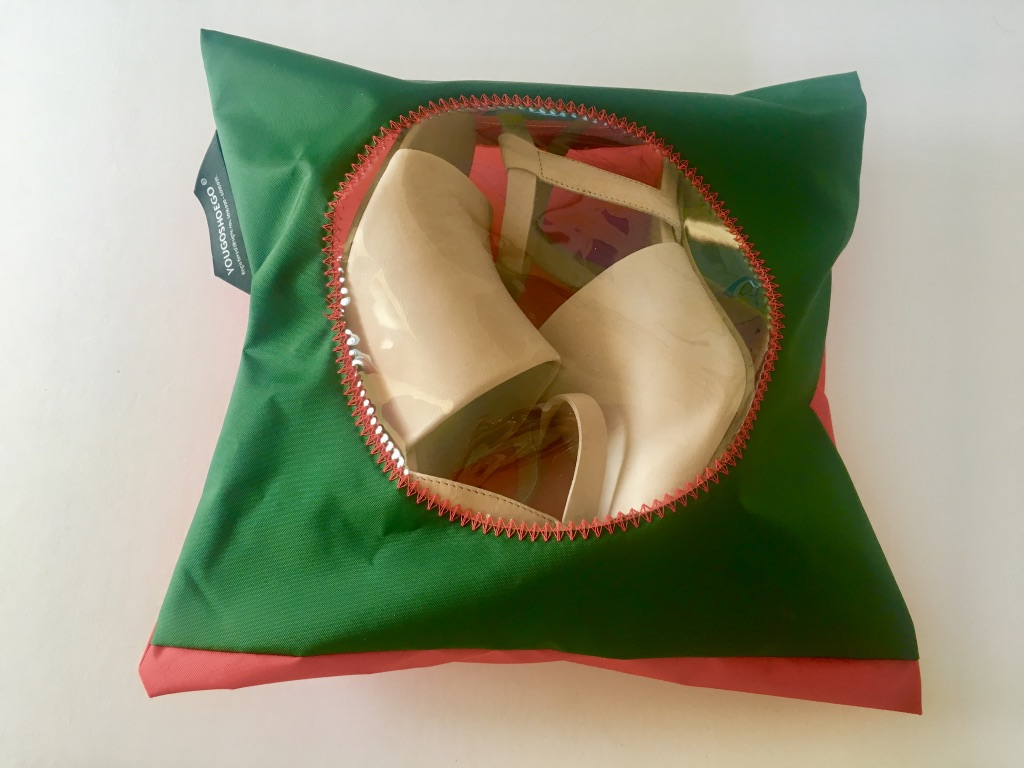 Lovely dark green and red pouch with a circular transparent window.  The hanging loop and zip closure provide perfect storage and protection for your shoes in your wardrobe and your shoes and clothes too in your suitcase.